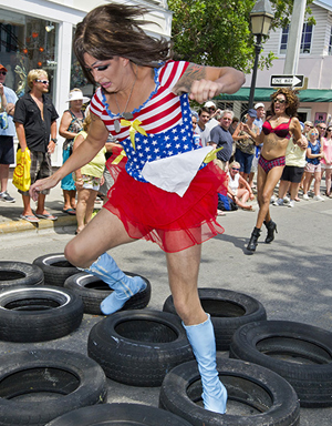"A female impersonator high-steps through tires after being pushed in a shopping cart during the Great Conch Republic Drag Race Saturday, April 20, 2013, in Key West, Fla. The hijinks was a facet of the 10-day Conch Republic Independence Celebration that continues through April 28 and marks the Florida Keys 1982 ""secession"" from the United States, following the Border Patrol's surprise roadblock at the top of the Keys Overseas Highway. FOR EDITORIAL USE ONLY (Rob O'Neal/Florida Keys News Bureau/HO)"